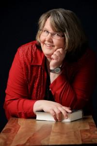 Porträtfoto von Nicole Gozdek, aufgestütztes Kinn und Buch in der anderen Hand