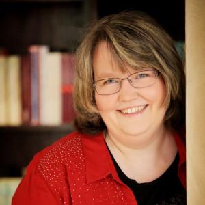 Portraitfoto von der Autorin Nicole Gozdek vor einem Bücherregal