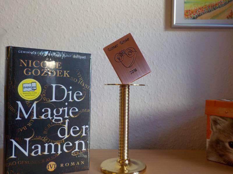 Preis aus Metall neben Buch