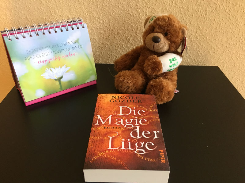 """Taschenbuch """"Die Magie der Lüge"""", Aufsteller mit Motivationsspruch und kranker Teddybär"""